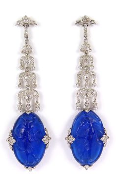 A pair of Edwardian diamond and blue cameo glass pendant earrings, circa 1905. Each hung with an oval blue panel featuring a neoclassical style lady, wearing flowing robes and holding a dancing pose, the relief to both sides, secured at the cardinal points by diamond set quatrefoils, below a diamond set four-tier chandelier, the foliate cluster tiers each with small swing collets, from a trefoil top, the diamonds all millegrain set. Length 6.5cm