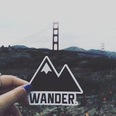 """@charitymoore holding our new """"Wander."""" sticker up by the Golden Gate Bridge. Follow her page for an upcoming giveaway! Also, check out our shop @ travelerkitandco.com"""