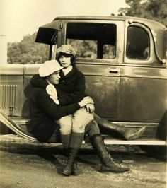 Fashion couple on running board of an old automobile, ca. 1920s