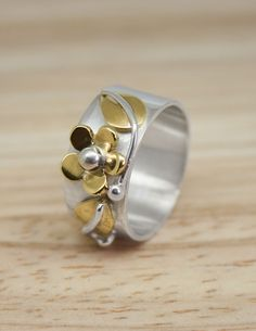 Silver flat band ring with brass flower and leaves