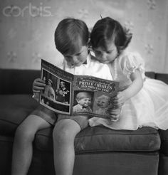 Prince Charles and Princess Anne reading a book about themselves at Buckingham Palace.  1953