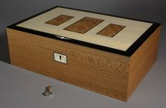 This is an Art Deco inspired box. It is made from quatersawn elm with elm burl panels on the lid which have fine black borders. The lid is borderd in black plastic with art deco polyester inlays. The trays are made from master grade curly maple and it is finished with several coats of shellac followed by wax. Dimensions: 300x200x100