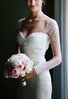 A gorgeous long-sleeved @pronovias wedding dress with sequins and beading | Brides.com