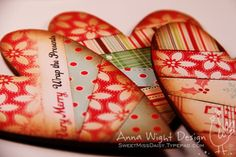 Wooden hearts covered in paper strips then mod podge and sand edges and distress ink