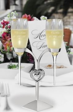 Two glass raindrop stem toasting flutes custom engraved with the bride's name and wedding date on one glass and the groom's name and wedding date on the other glass are suspended by a high polished silver plated toasting flutes holder with dangling heart centerpiece to create the ultimate wedding toasting set for the newlyweds to share during their wedding reception toasts.