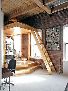 A raised platform with an overhead suspended storage loft separates a home office/private study area from the main space.