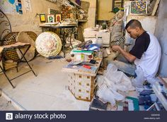 Download this stock image: Tangier, Morocco - August 20, 2014: Young craftsman makes tiles for a mosaic - G20HHD from Alamy's library of millions of high resolution stock photos, illustrations and vectors.