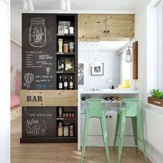 Inspirações para decorar usando lousa. Cozinha americana com a parede que dá para sala, com lousa para decorar. https://conexaodecor.com/2018/04/inspiracoes-para-decorar-usando-lousa/