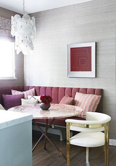 A custom-made channeled bench creates easy seating in the breakfast nook. The chair is by Kelly Wearstler, and the table is vintage with a rose-marble top and brass tripod base.