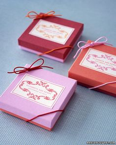 Mix and Match Boxed Favors    Play with color by swapping the lids on bright boxes. Affix printed labels, then tie contrasting elastic cording in bows and loop them around corners.