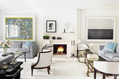 An understated white fireplace surround blends into the gallery-like living room of a New York City apartment decorated by Penny Drue Baird of Dessins. The rectilinear two-shelf mantelpiece complements the bold artwork and provides additional space to display sculpture and objects. (May 2011)