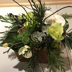 A feminine Texture Box with roses, succulents, Phalaenopsis orchids, cedar, fir and Tree Ivy, accented with privet berries, pinon cones and Magnolia branches.