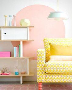 peinture décorative dessin géométrique - un grand pois de couleur pêche dans le salon avec des objets déco en couleurs pastel et un fauteuil en jaune vif