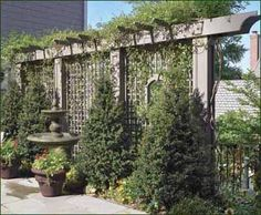 Custom Privacy Lattice - A delightful garden fountain is complemented on either side by custom lattice panels. They sit snugly within the curving wall and encourage greenery, adding further color to the setting.