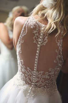 A close-up wedding photo of the bride getting ready. She wore a sleeveless illusion back wedding dress with beaded embroidery and a column of buttons worn with a loosely curled half up-do.