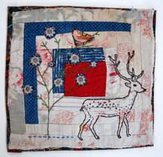 """''The support for the piece is a very old piece of log cabin quilt featuring a turkey red centre square. I have """"drawn"""" a deer using hand embroidery and small extra pieces of fabric have been appliquéd in to this as well as on to the background to form a tree/flower setting for the deer. The patchwork is very uneven so the piece isn't perfectly cut or square but this adds to its charm.The edges are fraying a little bit and this is also intentional.'' by Mandy Patullo"""