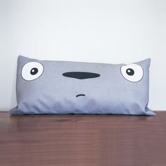 Hello, Totoro. Greet your neighborhood forest spirit every day with this pillow on your bed or sofa. With his simple and nostalgic charm reminiscent of childhood, you'll have a smile on your face with a Totoro in your home.