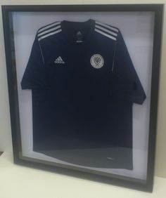 Sports shirt framed simply in a deep black frame on a white back board.
