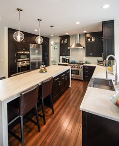 White Macaubas Honed quartzite countertops with a box mitre edge detail and waterfall panels on the island. A glass tile backsplash and espresso cabinets complete this contemporary look. Kitchen by Stoneshop from Cherry Hill, NJ.