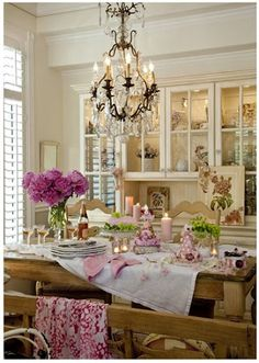 Dining room with nice flowers in vases.  Could be a nice potting bench too.   Nice setting with flowers and candles.  Beautiful picture, setting and room!