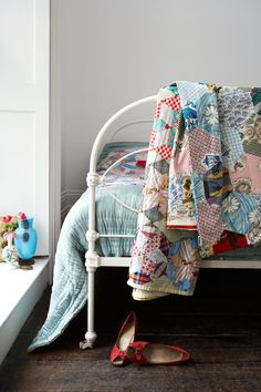 Patchwork quilts and an iron bed for a beautiful vintage bedroom. Rachel Whiting Photography