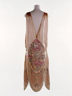 This embroidered satin dress in a Chinese style is one of Norman Hartnell's earliest known designs. Hartnell opened his couture house in Mayfair in 1923 and rapidly gained a reputation for making exquisite evening gowns. There is a strong streak of theatricality in all his clothes and Hartnell began his design career working for the theatre. He continued to design lavish gowns for actresses to wear on and off the stage throughout his life. Production Date: 1924-1926