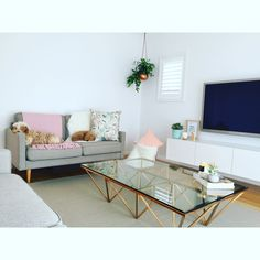 Scandi Love, Scandinavian decor, copper coffee table, white gloss floating tv unit, my style. Pastel colours, hanging Millie archer pot plant. Grey London couches with wood peg legs. Low pile woven beige rug