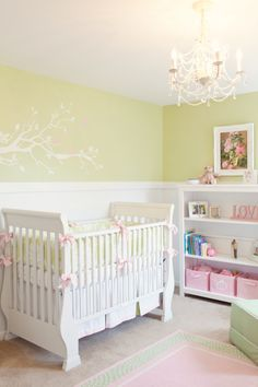 Now this is a nursery!!! Love the wall decals, the chandelier and the subtle pops of pink against the neutral tones of beige and white.
