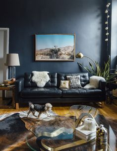 Dark and moody living room with dark walls, black sofa, cowhide rug, and bright desert photography. Dark Living Rooms, Living Room Paint, Living Room Decor, Dark Rooms, Black Couches, Black Sofa, Navy Sofa, Dark Walls, Blue Walls