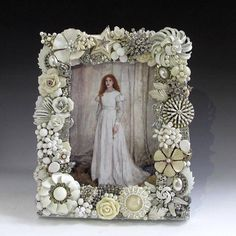 A stunning all white frame, it is composed of over 30 pieces of vintage costume jewelry-most are midcentury pieces. Find enamel on metal flowers, milk glass, china roses, pearls, crystals, clear rhinestones on silver tone metal and more. It has a pearl white wood frame and a sturdy
