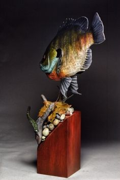 Hand carved and painted Bluegill male. Branch, eyes, rocks, leaf and leech also hand carved and painted. Yves Laurent 2020