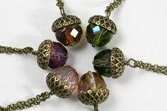 This acorn necklace features a faceted crystal with an antiqued brass acorn cap. All are wrapped in antique brass wire and hung from a delicate 16