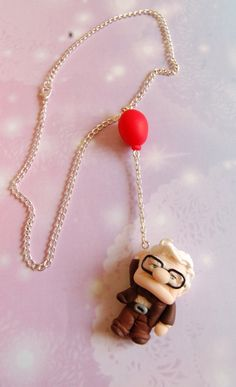 Handmade Up! necklace with polymer clay Carl hanging by the balloon. The chain is nickel free and silver plated.