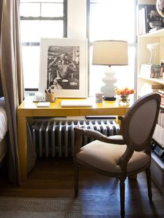 Lonny Blog. Yellow West Elm Parsons desk.  French louis chair from Wisteria.  Small studio apartment.  Desk on top of radiator. Ikea billy bookcase in white. studio apartment in NYC. Manhattan studio apartment. Studio apt.