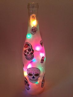 LEARN MORE Sugar Skull themed frosted light comes complete with your choice of bulb color. (UL Listed bulbs) 20 strand mini lights are electric & plug in to any power outlet. The cord comes thru the hole that is drilled in the back of the bottle.