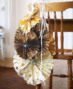 木製の椅子の背に掛けたゴールドのホリデーデコレーション。