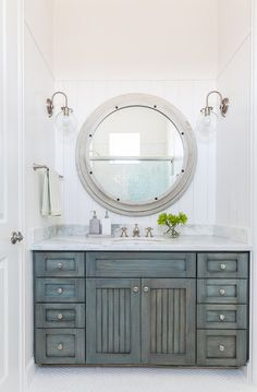 Distressed Bathroom Cabinet. This bathroom features vertical shiplap walls lined with a large gray wood mirror illuminated by clear glass barn sconce over a gray distressed washstand topped with white marble fitted with an oval sink and satin nickel faucet. #Bathroom #Distressed #Cabinet Laura U, Inc.