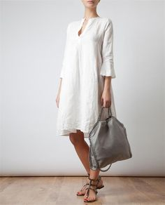 Perfect on a hot summer's day whether walking to workor a strollalong the avenue this simple white linen tunic complements any age and flatters every figure.