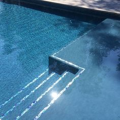 This wet deck is sparkling with beautiful glass tile and Mediterranean hydrazzo inviting the new home and pool owners in for a welcome swim! #adghafp