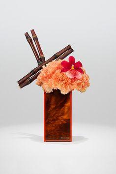 Orange Dianthus, sugar cane and red Cambria orchid on turtle plexiglass vase Armani Flowers