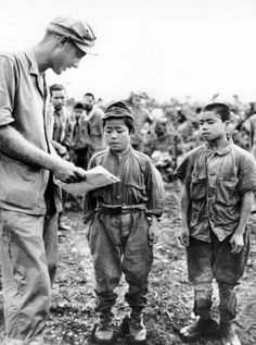 U.S. Marine 1st Lt. Hart H. Spiegal tries to communicate with two very young Japanese soldiers captured during the Battle of Okinawa. June 17, 1945.