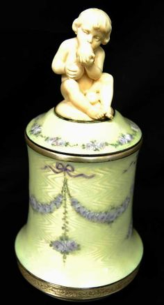 Signed Faberge ~ Dresser jar ~ With ivory carved baby ~ Trimmed around the lid are little purple flowers ~ Draped little purple flower wiith chadelier sprays hanging from the drapes ~ gilt gold trimmings All done on a off white guilloche enamel background