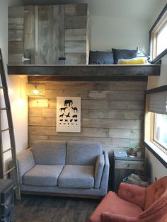 "The tiny house living room has space for a couch and chair, plus it has a beautiful wood accent wall. The bedroom loft is 11 1/2 feet long and 8 feet wide and the second loft is 32"" deep with a storage chest and reading nook by the window."