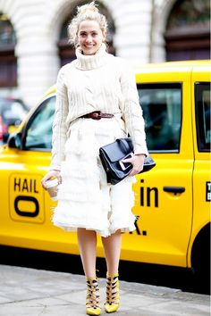 A fringe skirt and lace-up heels add flair to a knitted turtleneck.