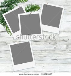 Blank instant pictures on grey wooden background decorated with fir branch; Placeholder for christmassy moments - stock photo