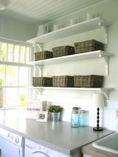 Counter top on top of front loading machines for extra work space and multiple shelves with baskets to hold supplies.