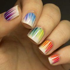 Estilosas uñas decoradas en color beige y adornadas con líneas de colores, en tonos morados, azules, verdes, amarillos, rojos, naranjas y rosas.