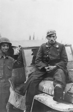 """A captured German guard sits on top of a jeep, while an American soldier Julius Bernstein stands on his right.    The original caption reads, """"German guard I captured hiding in a latrine. A few minutes after this photo was taken, I was marching the prisoner to an MP truck to be taken away to a POW Interrogation point when one of the 12 survivors sneak-up behind me and the prisoner and sinks a piece of 2x4 in to his head. He was dead before he hit the ground""""."""
