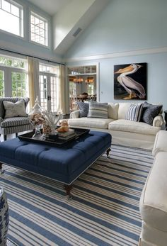 hamptons style room, blue stripe rug... lovely coastal feel, love the Audubon picture and shells... Love the blue and white theme, and the windows... ralph lauren blue - living room...