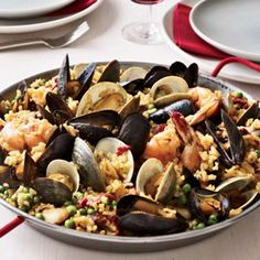 Seamus Mullen cooks the rice for this chicken-and-seafood paella as if it were risotto, adding chicken stock gradually. Stir stock or canned chicken broth into the rice all at once and cook.